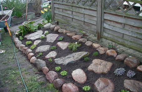 Stenbed med store sten og planter.